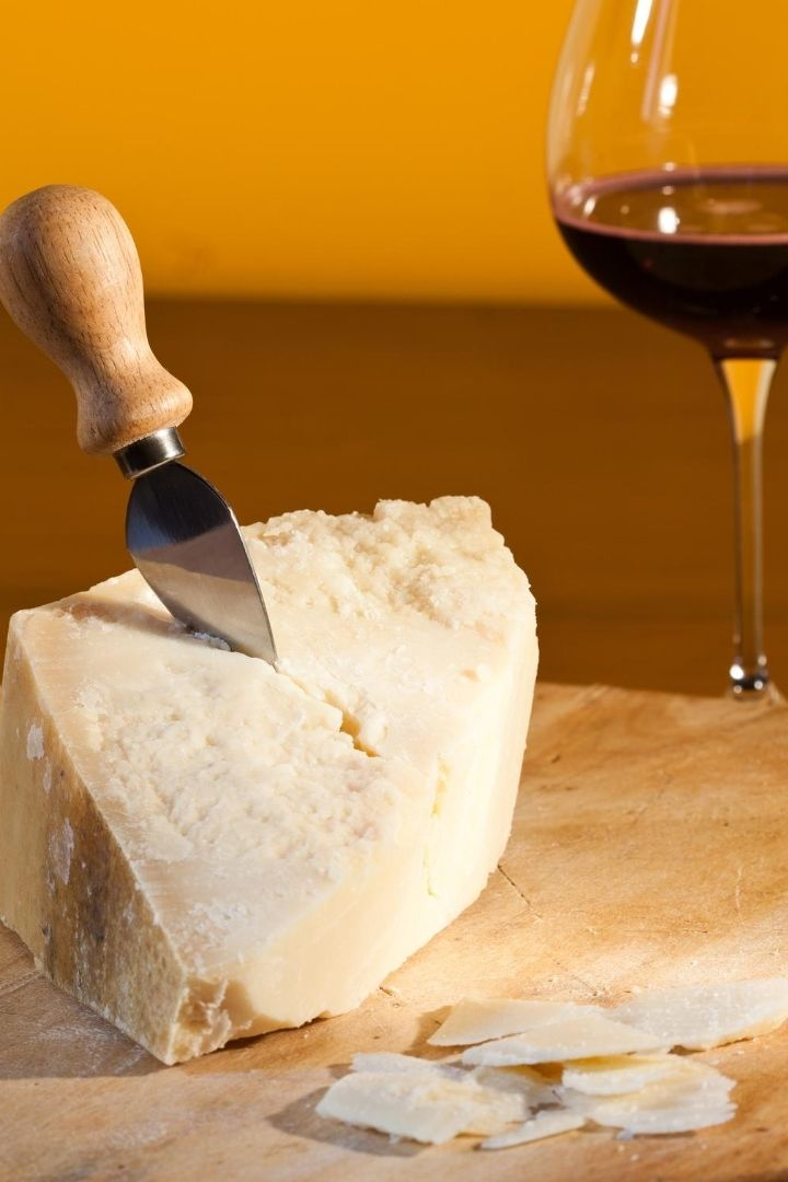 Grana Padano on wooden board and glass of red wine, 13 Most Popular Italian Cheeses - The Proud Italian