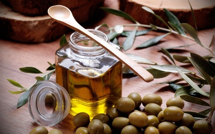 Extra virgin olive oil in jar with olive berries, Olive Oil vs. Extra Virgin Olive Oil - The Proud Italian
