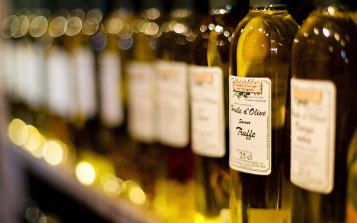 Row of fresh olive oil in bottles, Olive Oil vs. Extra Virgin Olive Oil - The Proud Italian