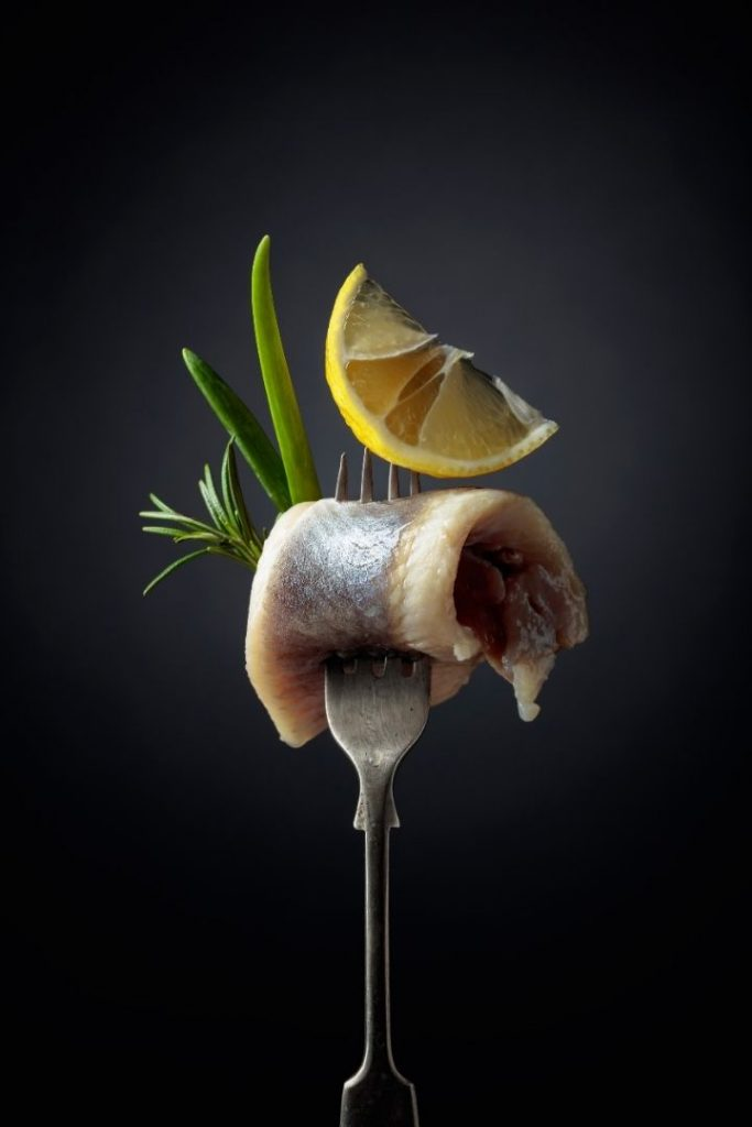 Atlantic Herring slice on a fork with slice of lemon and branch of rosemary - The Proud Italian