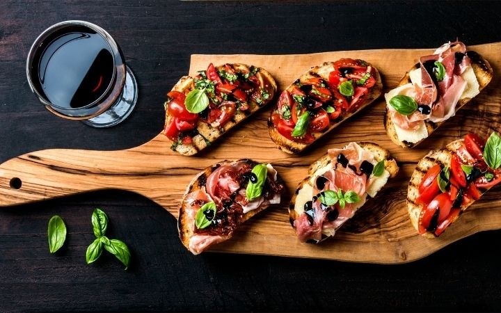 Overview of bruschetti on wooden plate, with a glass of wine besides - The Proud Italian