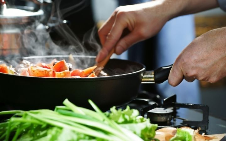 View of someone's hands holding a cooking pan with vegetables inside and besides the stove - The Proud Italian