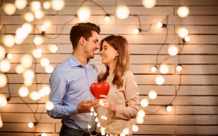 Young couple celebrating Valentine's day with lanterns and holding a heart together - The Proud Italian
