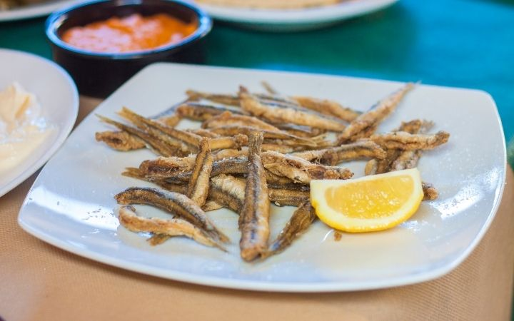 European anchovy fried and served on the plate with a slice of lemon - The Proud Italian