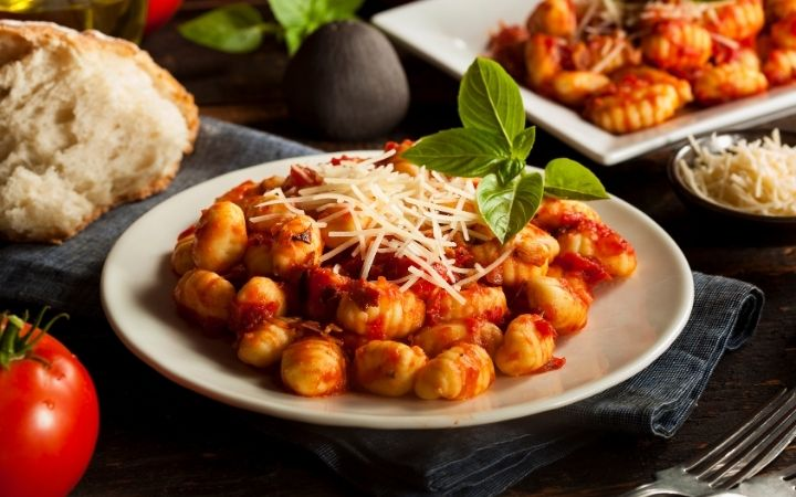 Gnocchi with red sauce and cheese grated on top - The Proud Italian