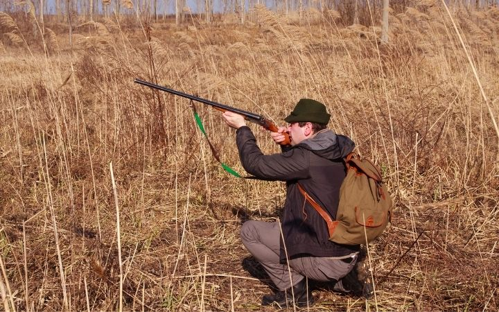 Man hunting, aiming with a gun - The Proud Italian
