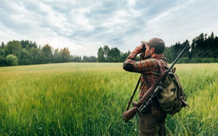 Man in hunt with gun on his back on a field, looking through binoculars - The Proud Italian