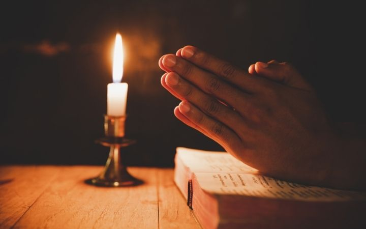 Man's hand praying on the Bible with candle in the background - The Proud Italian