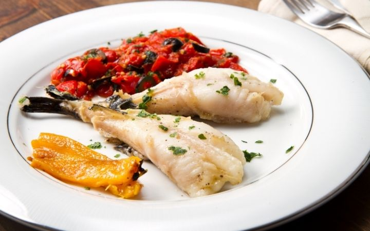 Monkfish dish on plate with slices of grilled peppers on the side - The Proud Italian