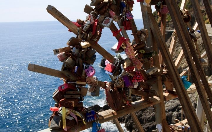 Padlocks on rails in Cinque Terre, with sea in the background - The Proud Italian