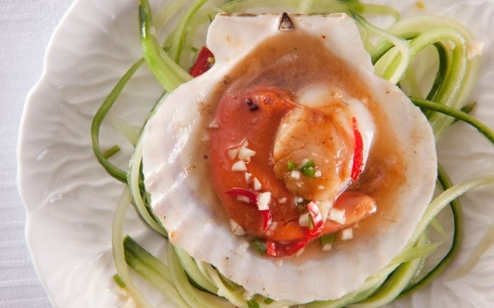 Pilgrim scallop dish served on the plate with slices of zucchini - The Proud Italian