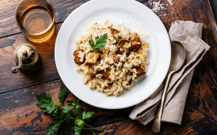 Risotto with mushrooms served on the plate with a glass of wine, cloth napkin, spoon, pepper and parsley beside - The Proud Italian