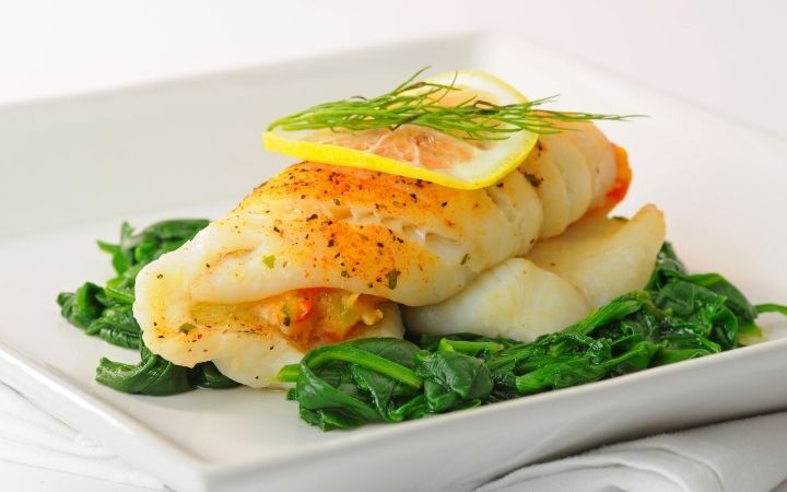 Stuffed Sole fish dish on the plate with steamed green leafy veggies and thin slice of lemon on it with a branch of rosemary - The Proud Italian