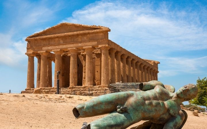 Temple in Sicily and broken statue in front of the camera - The Proud Italian