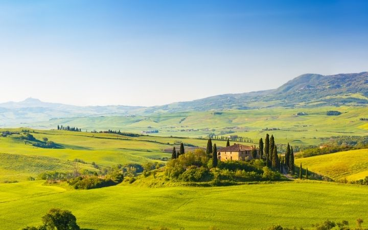 Tuscany landscape, fields, hills in the back and house surrounded with trees - The Proud Italian