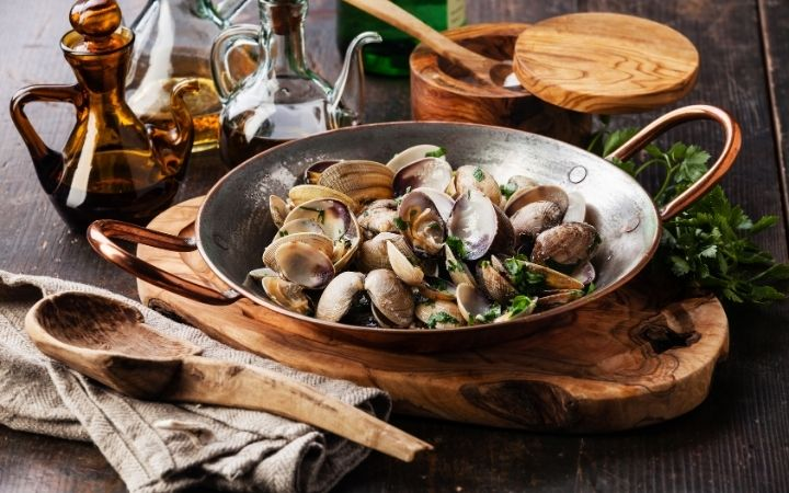 Venus clams in cooking pan on chopping board, wooden spoon, parsley, wooden bowl or salt and bottles of oils - The Proud Italian