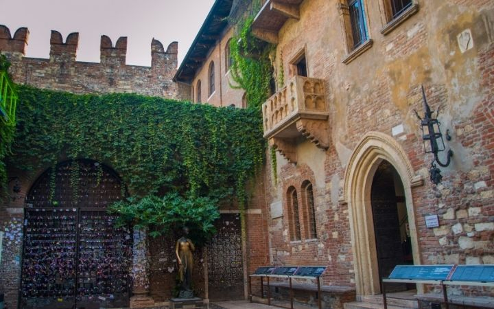 Front of the house of Juliet in Verona, with balcony and statue of Juliet and some ivy as decoration on the house - The Proud Italian