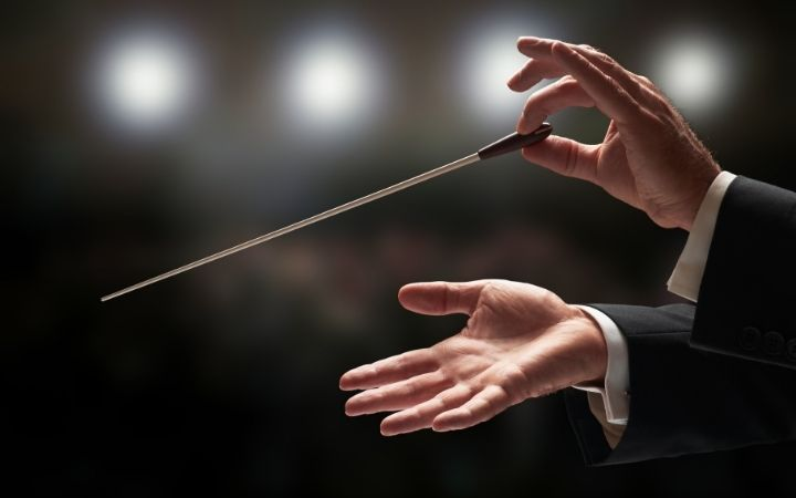 Conductor conducting an orchestra - The Proud Italian