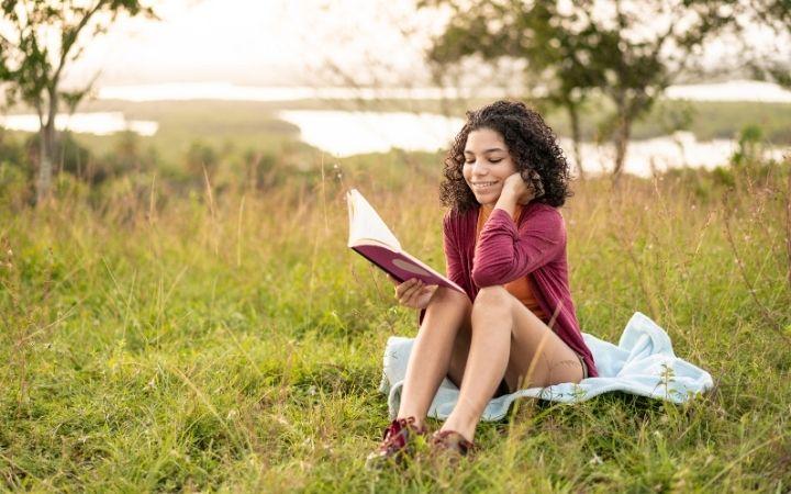 Girl reading Italian fairy tale in the field - The Proud Italian