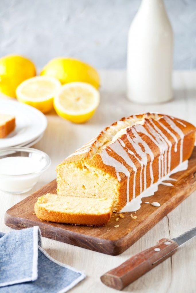 Italian lemon pound cake on cutting board with knife, milk and lemons beside - The Proud Italian
