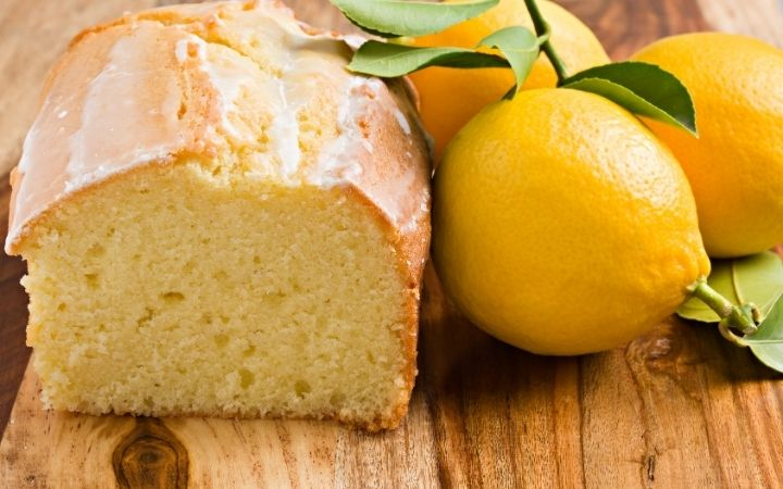 Italian lemon pound cake cut in half and a couple of lemons beside - The Proud Italian