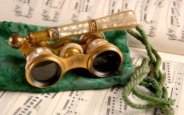 Opera glasses on green velvet atop on music sheet - The Proud Italian