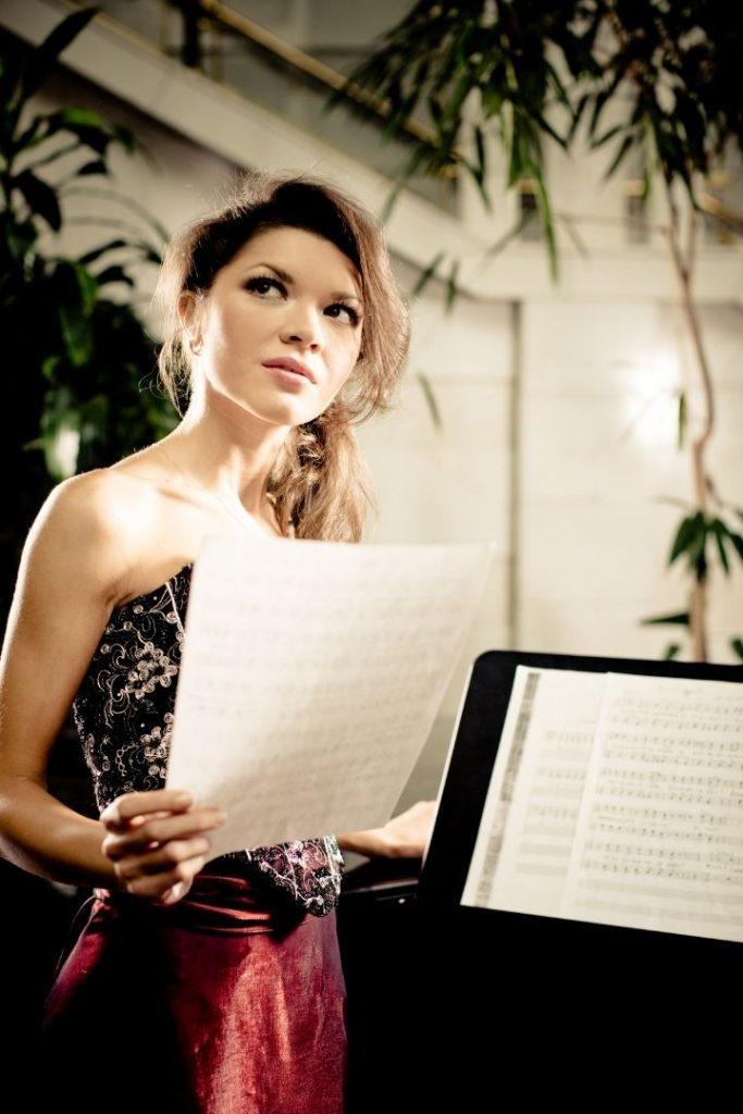 Opera singer holding music sheet beside a piano - The Proud Italian