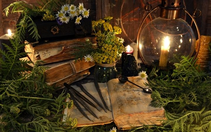 Spell book with herbs and candle beside - The Proud Italian