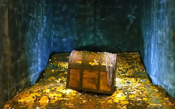 Treasure chest on a stack of gold coins - The Proud Italian
