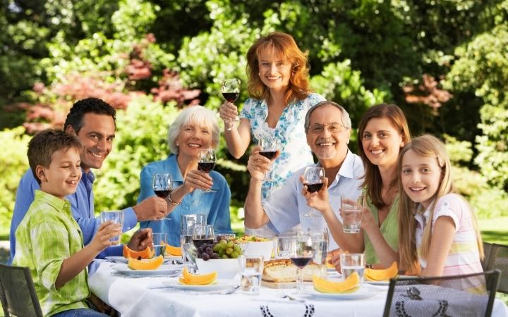Family reunion holding glasses of wine up - The Proud Italian