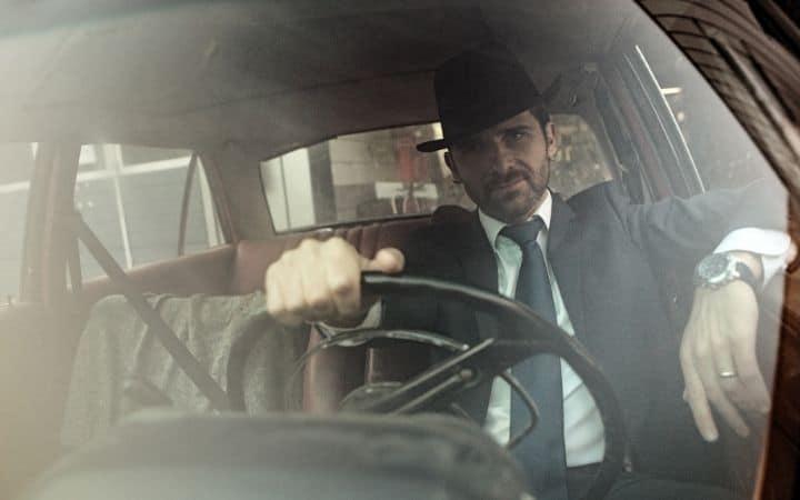 Italian man in the suit driving a car - The Proud Italian