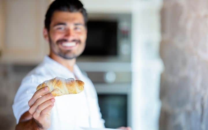 Italian man holding a pastry - The Proud Italian