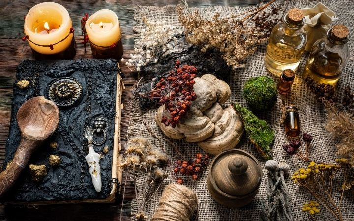 Witchcraft practicing, old book, candles, tinctures, herbs  on the table - The Proud Italian