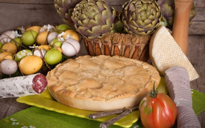 Italian Easter pie served on a plate with dyed eggs, artichokes, sausage, cheese, and tomato beside - The Proud Italian