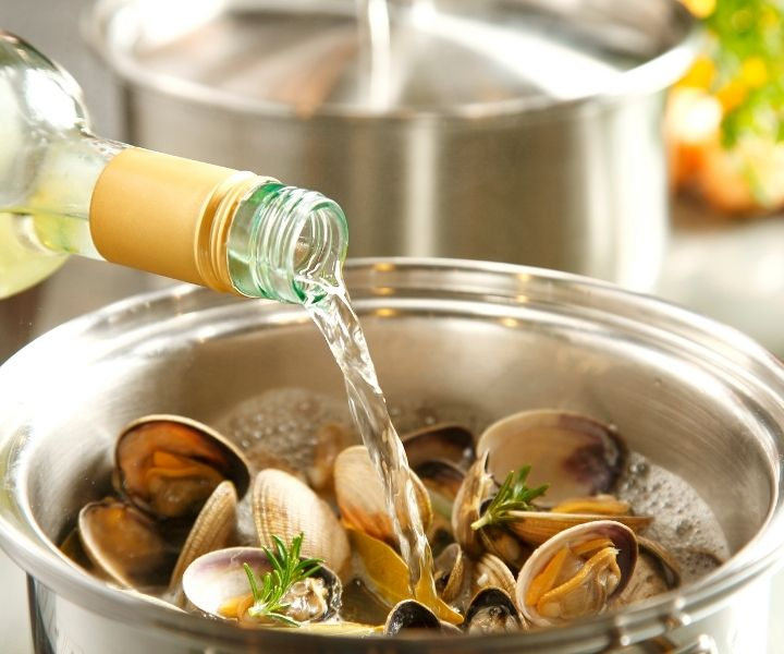 adding white cooking wine to a pot of muscles